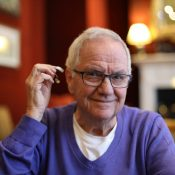 Senior man about to insert his hearing aid while wearing glasses