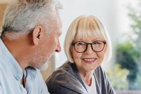 Senior couple smiling and looking over medical paperwork