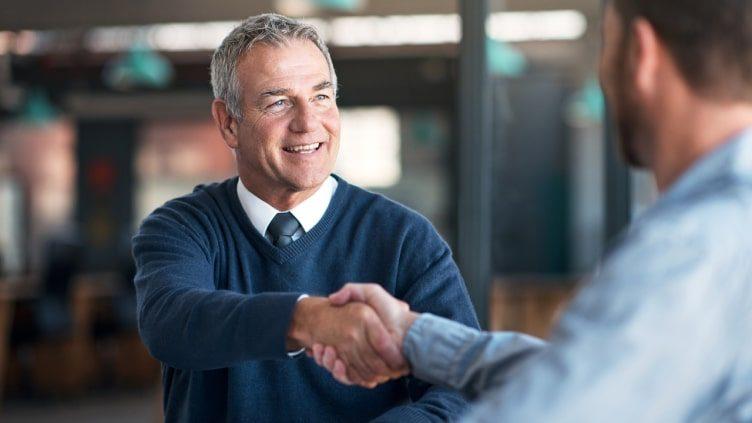 Older man shaking hands with advisor