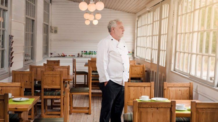 older man standing in empty restaurant