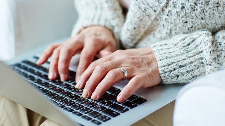 Older woman typing on laptop