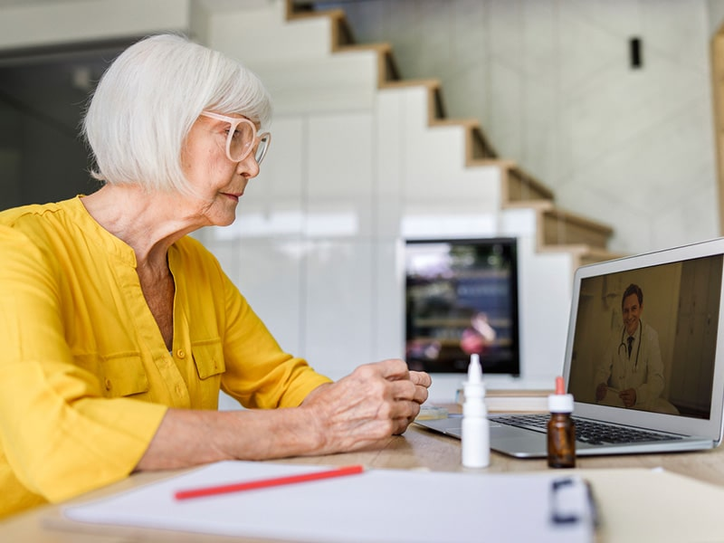 older woman using telehealth service and talking to doctor through laptop