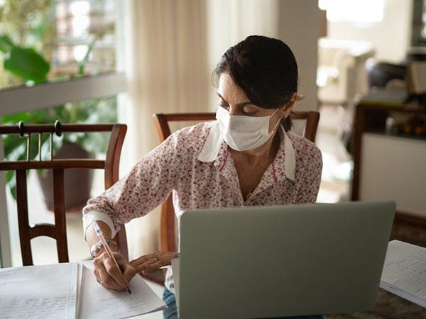 Older woman in masking writing