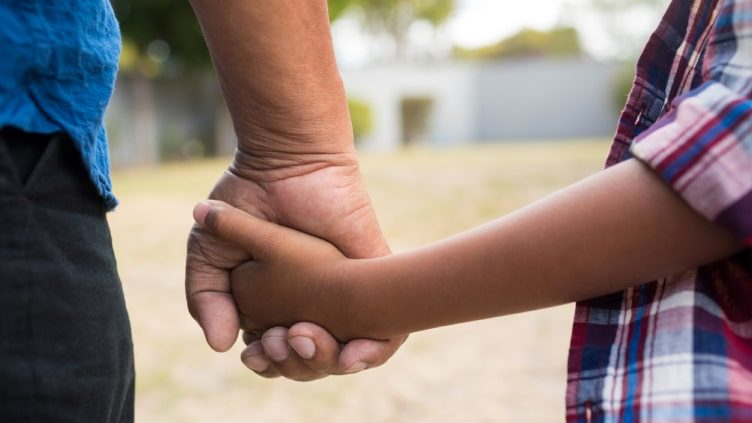 Boy and grandfather holding hands