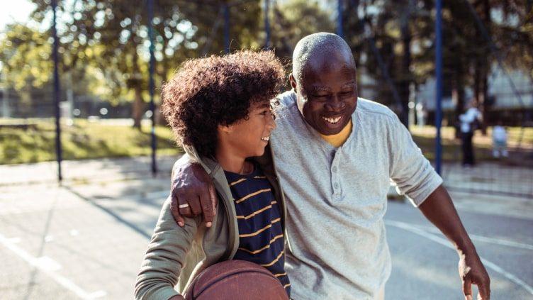 Grandfather playing basketball with grandson