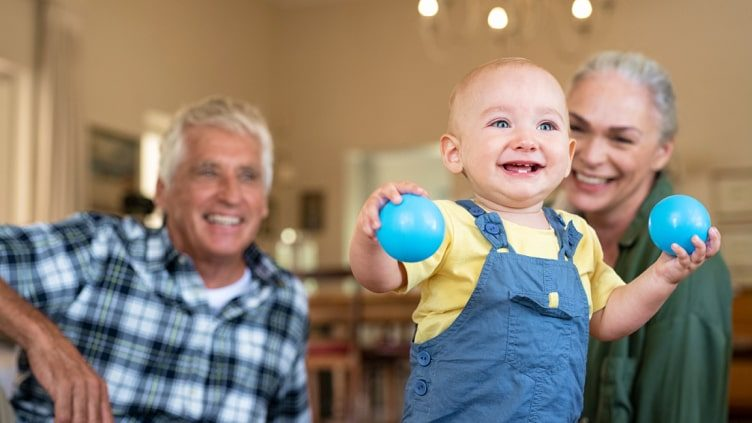 Grandparents watching toddler walking with toys