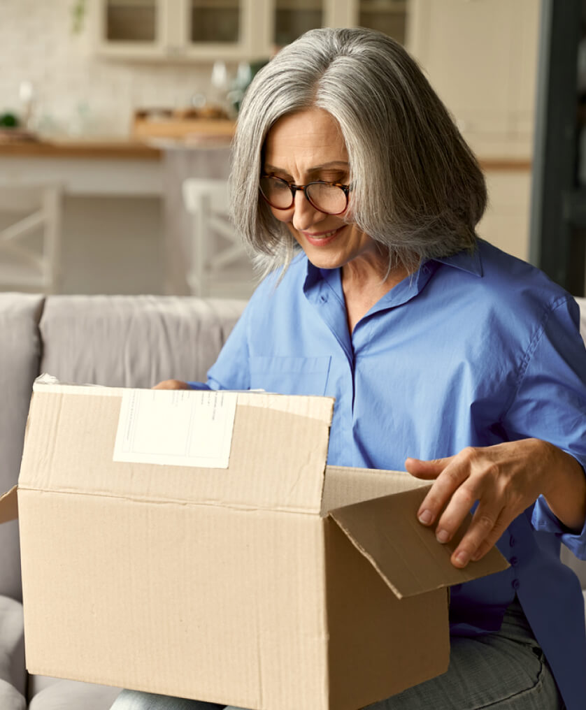 Elderly woman packing up a box