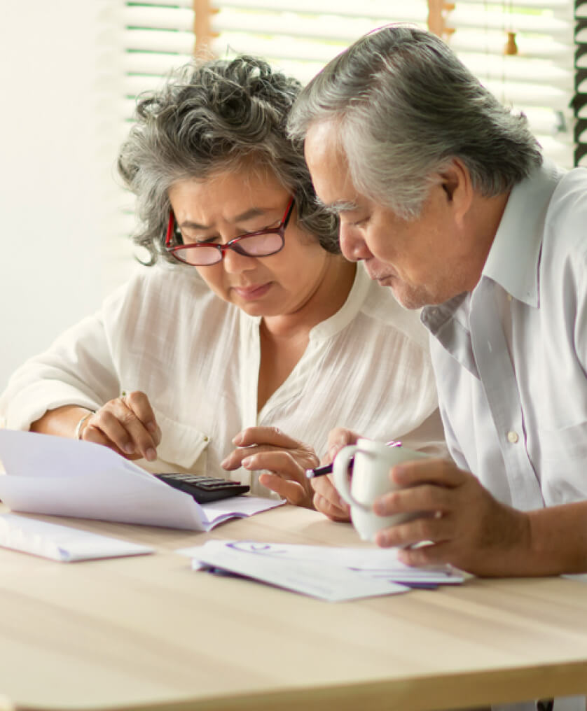 Elderly couple reading documents at a table