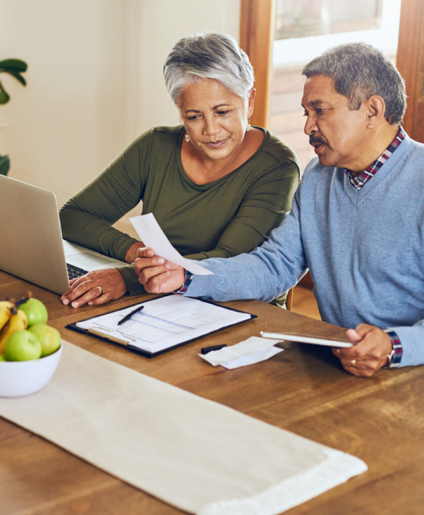 Elderly couple working on taxes at the dining room table
