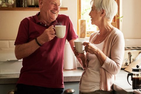 Elderly couple enjoying coffee in the kitchen together