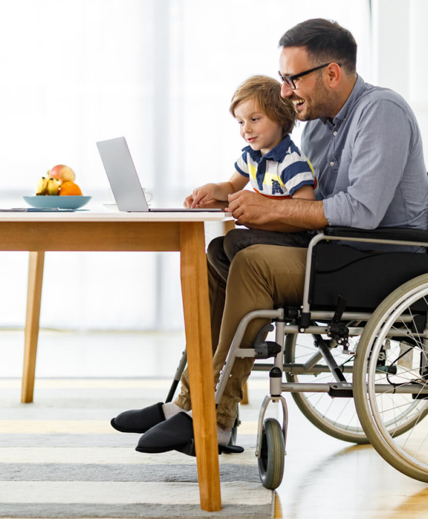 Man in wheelchair on laptop with his son in his lap