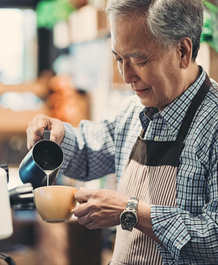 Elderly man pouring cream into a coffee cup