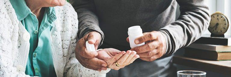 older man offering older woman medication