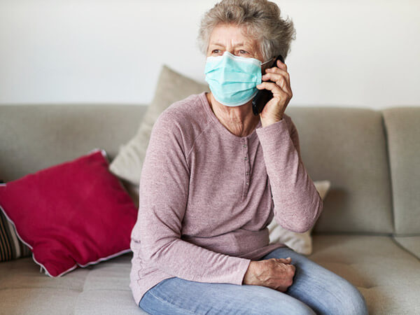 Older woman in mask using cell phone