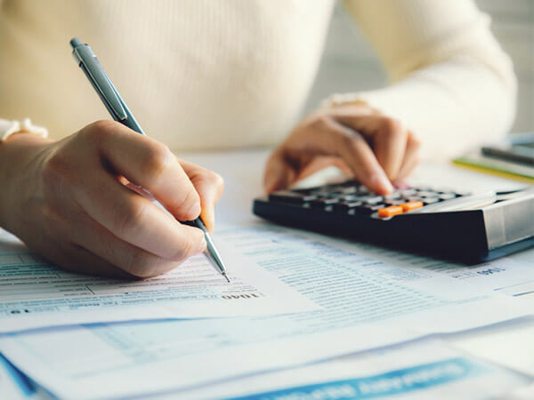 Closeup of woman filling out tax return form