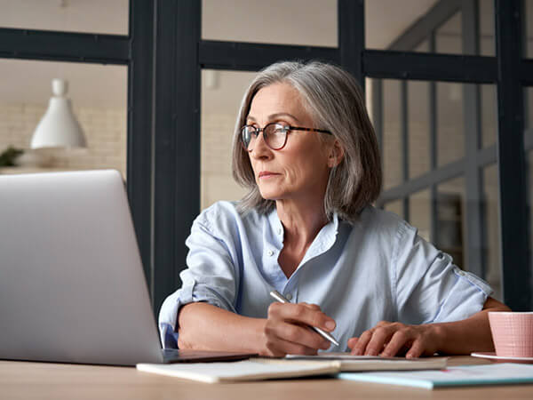 Older woman looking at laptop and taking notes