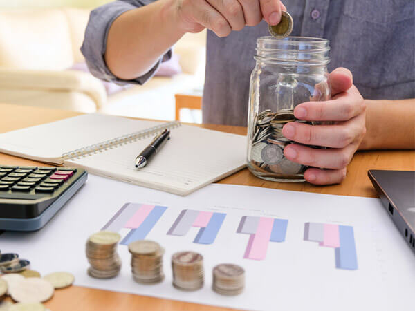 Older man saving coins in a jar