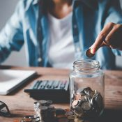 Young person saving coin in a jar