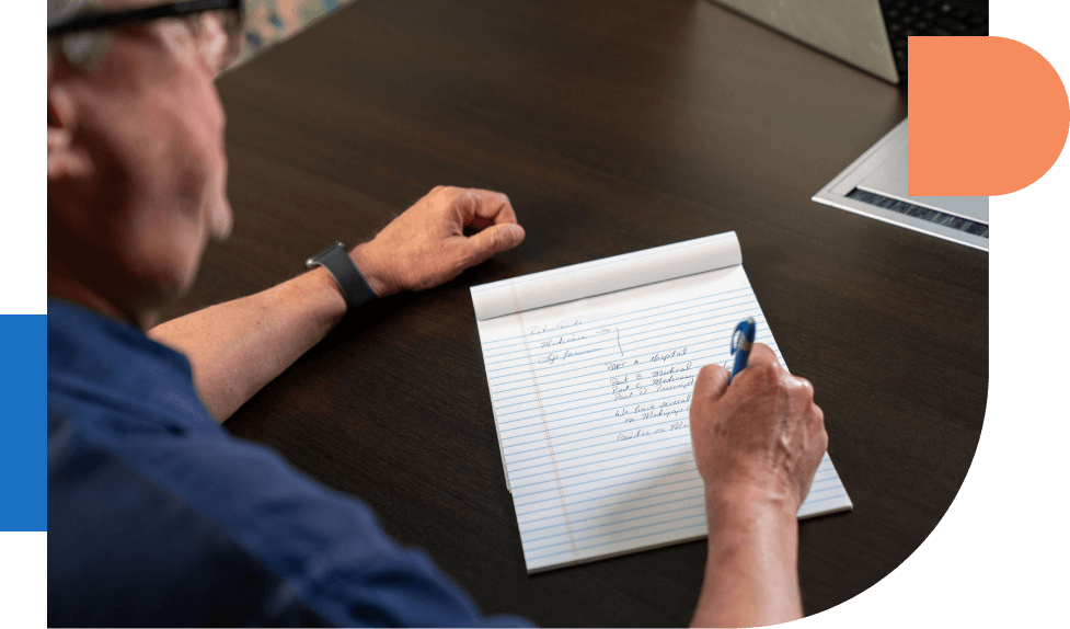 Man writing notes on paper pad