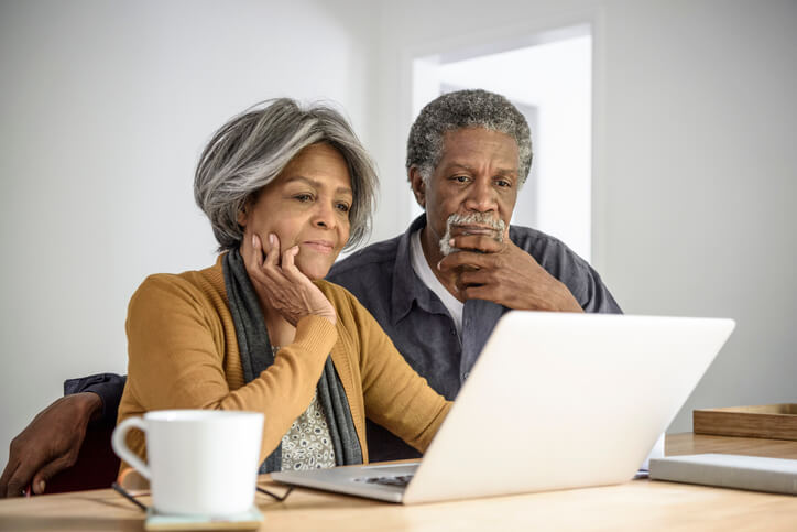 Senior African American couple looking at a laptop, worried over retirement finances