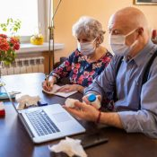 Senior couple consulting with a doctor on laptop at home